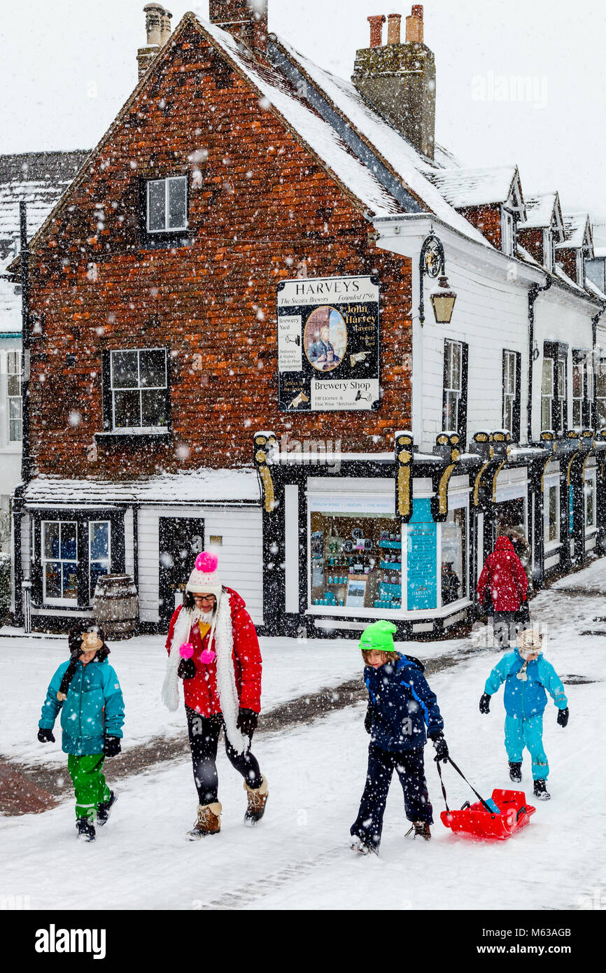With local schools closed due to the bad weather a family take time to go sledging, High Street, Lewes, Sussex, - Stock Image