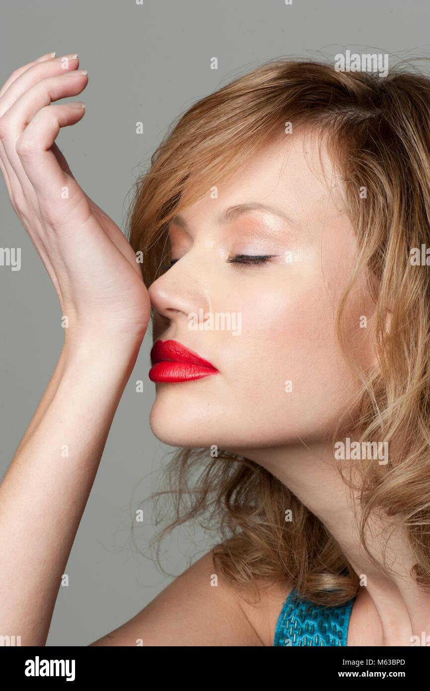 Woman smelling wrist - Stock Image