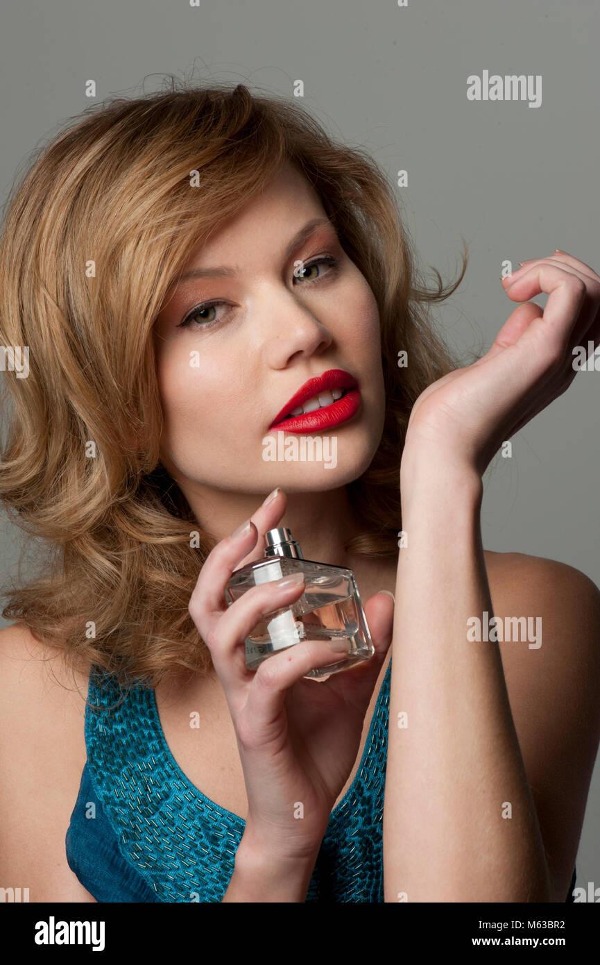 Woman spraying perfume on wrist - Stock Image