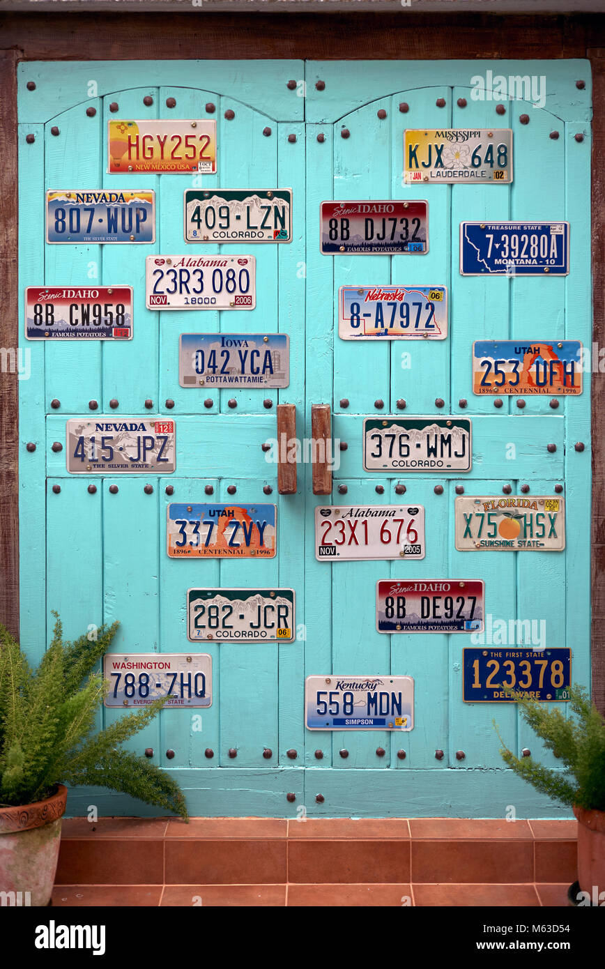 House door adorned and decorated with various American car number plates. USA license plate. - Stock Image
