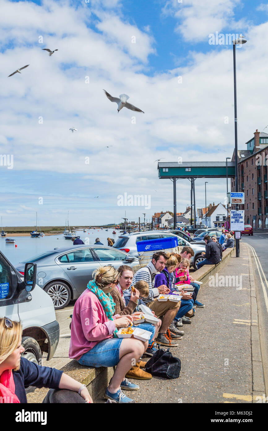 Enjoying fish and chips on the quayside at Wells next the Sea. - Stock Image