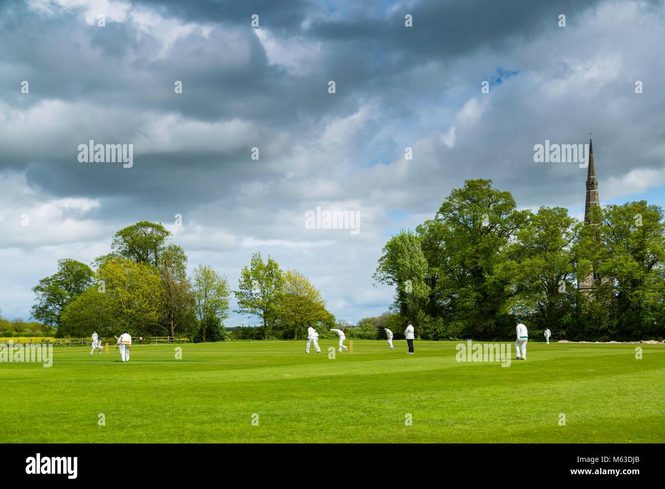 A cricket match on a village field under a stormy spring sky. - Stock Image