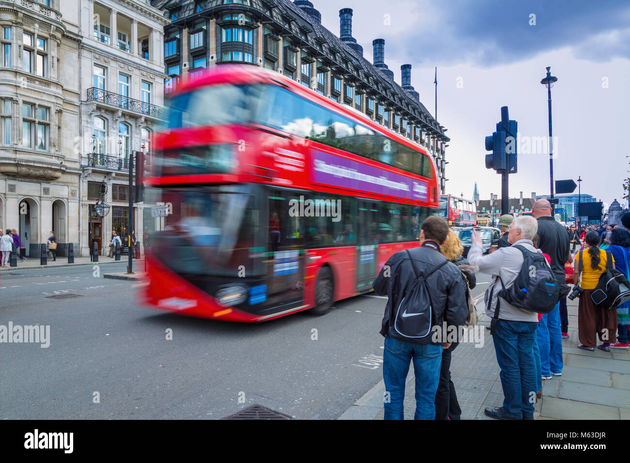 A new Routemaster bus speeds past pedestrians in Westminster. - Stock Image