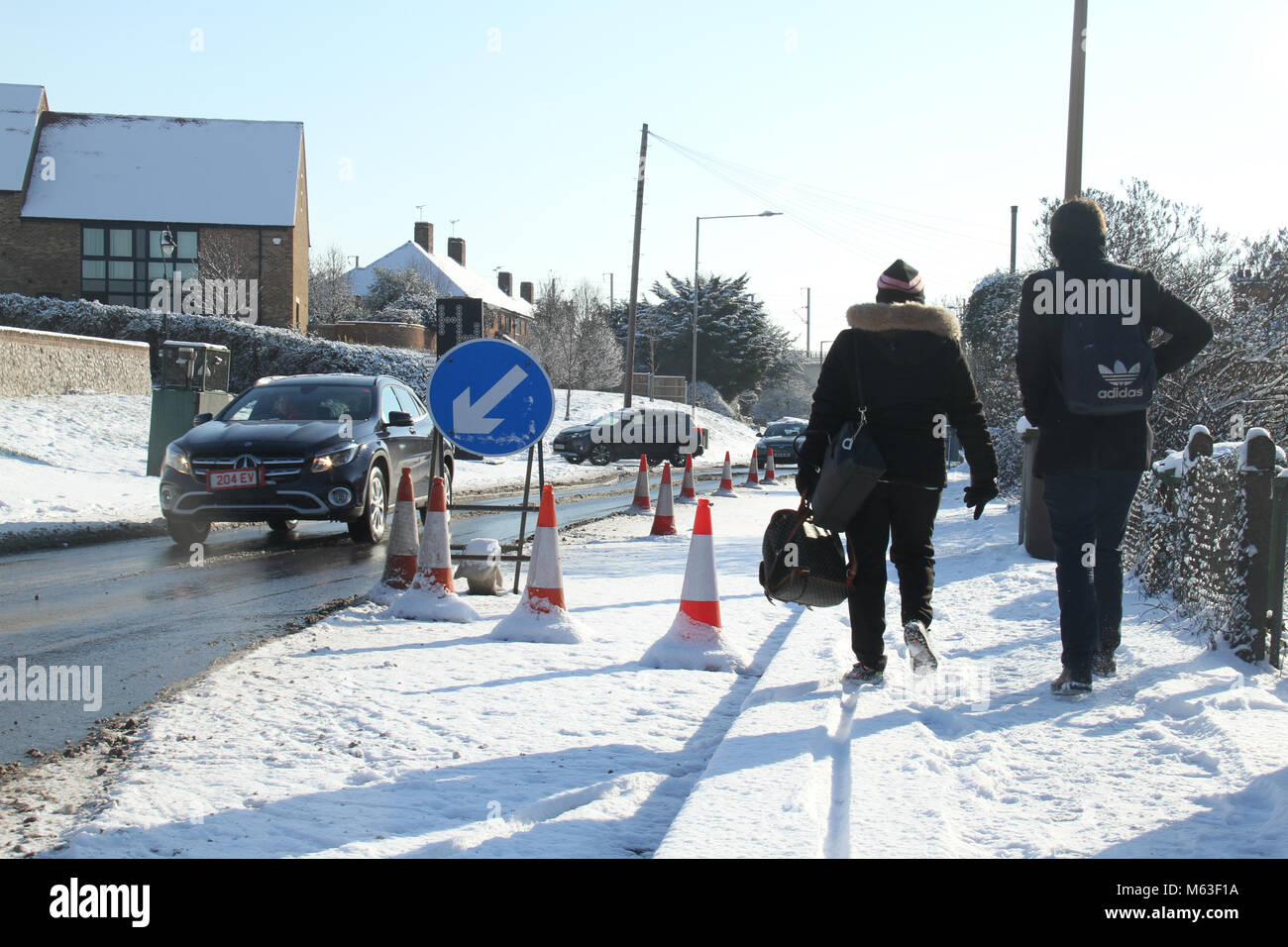 Purfleet, UK - February 28: Pedestrians walk by a snow-covered road obstruction on London Road in Purfleet on 28 - Stock Image