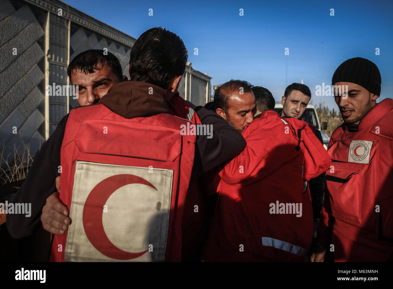 Members of Syrian Arab Red Crescent greet each other during an evacuation of Pakistani national Mahmoud Akram and - Stock Image