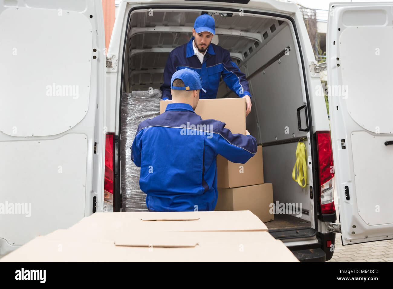 Two Young Male Movers Carrying Cardboard Box From Truck - Stock Image