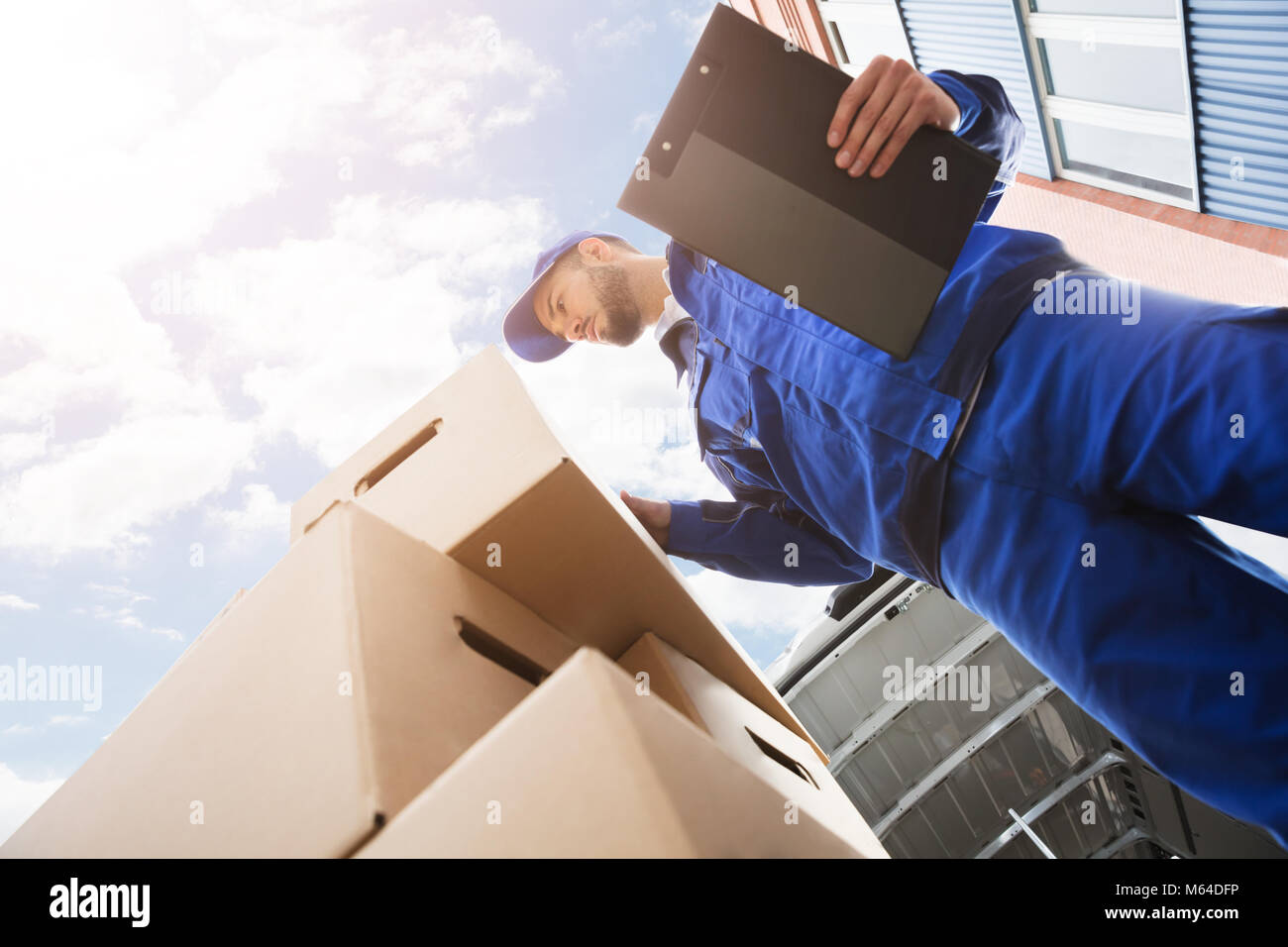 Low Section Of Young Male Worker Standing Near Cardboard Box Holding Clipboard - Stock Image