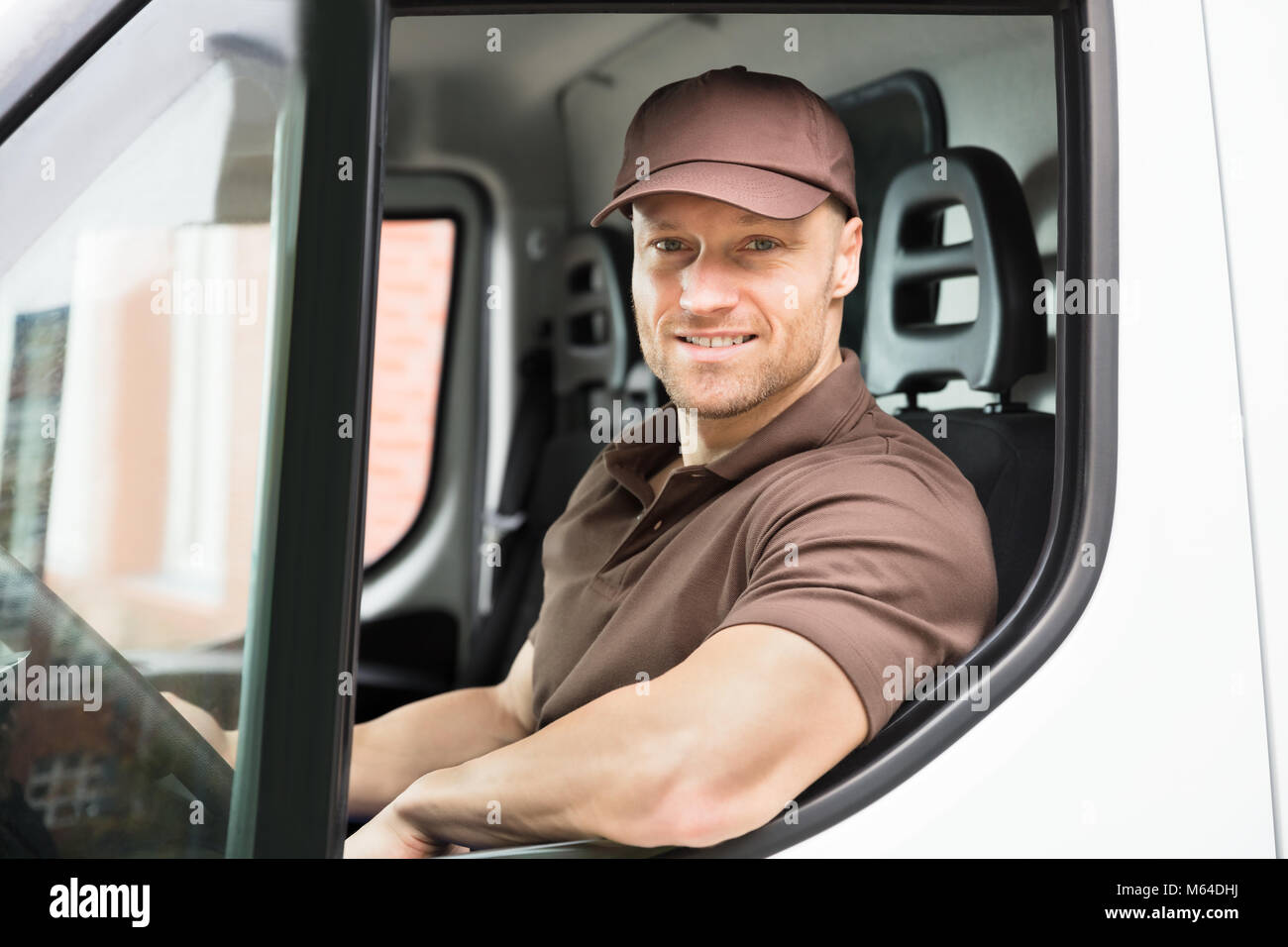 Portrait Of A Happy Young Delivery Man Sitting Inside Van - Stock Image