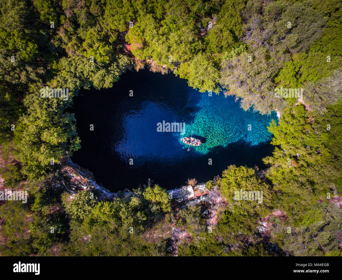 Melissani Cave Kefalonia viewed from above with tourists entering the cave by boat - Stock Image