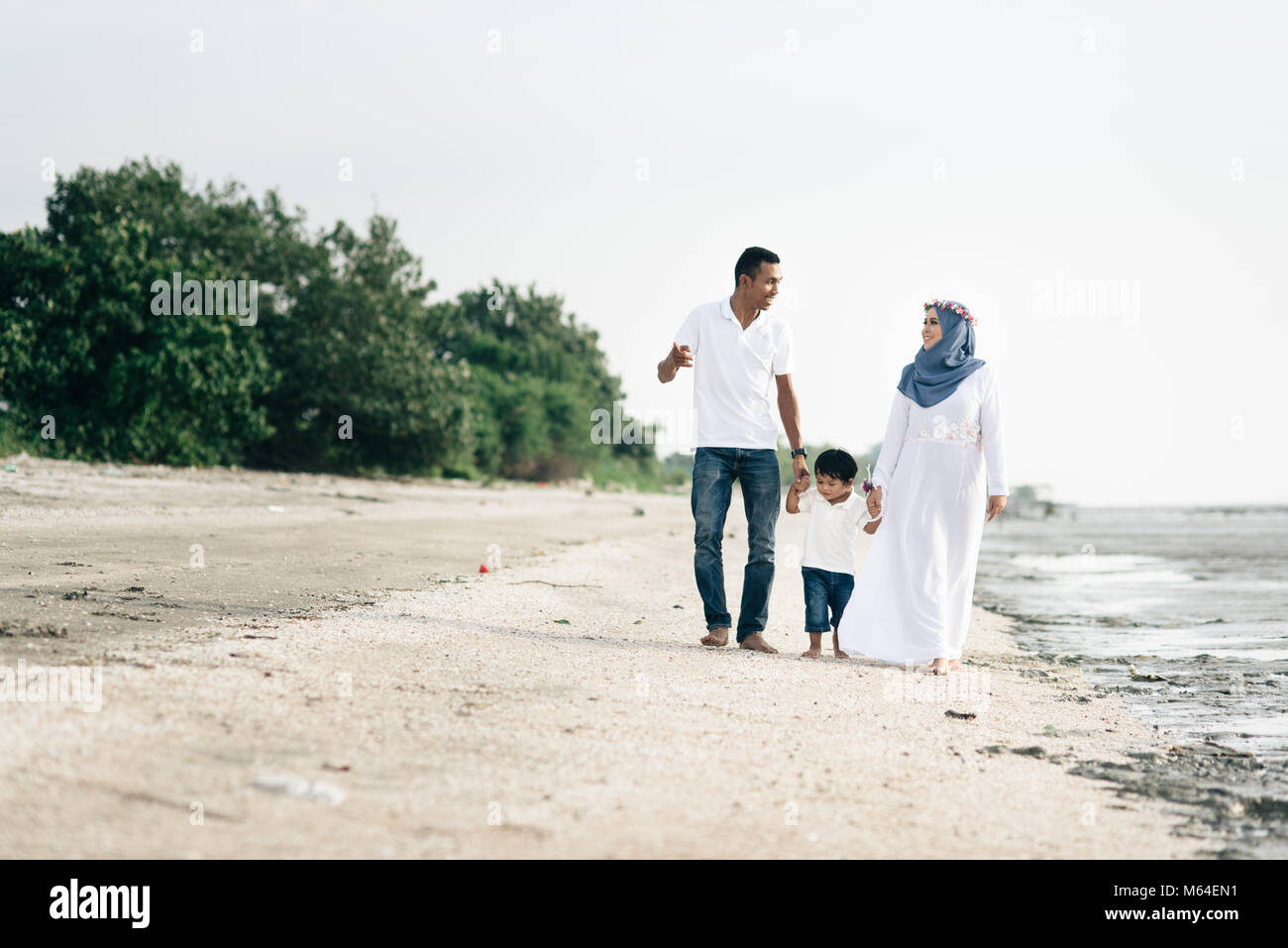 happy family having fun time walking together at the beach located in Pantai Remis,Kuala selangor,selangor,malaysia. - Stock Image