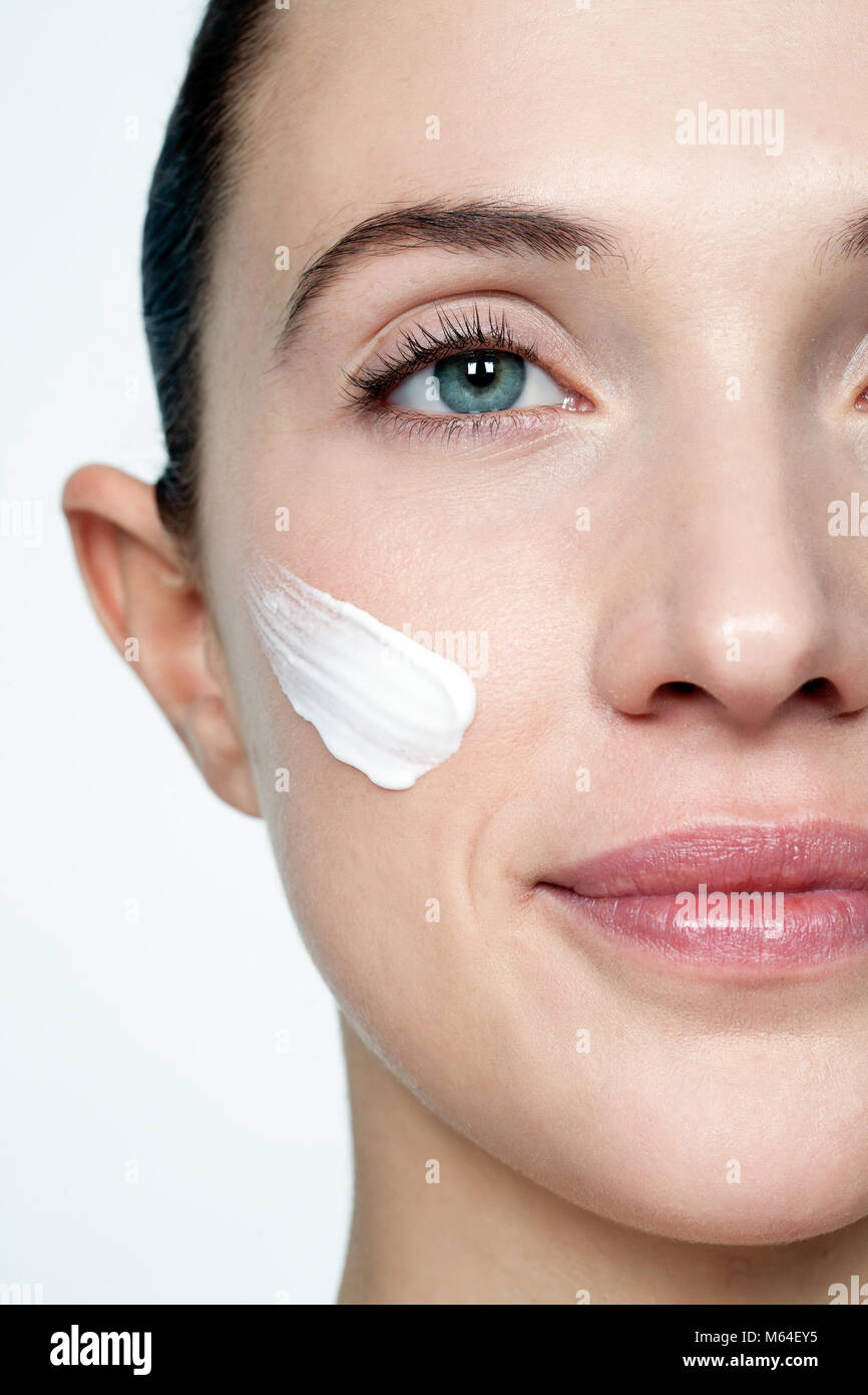 Cropped woman's face with cream - Stock Image