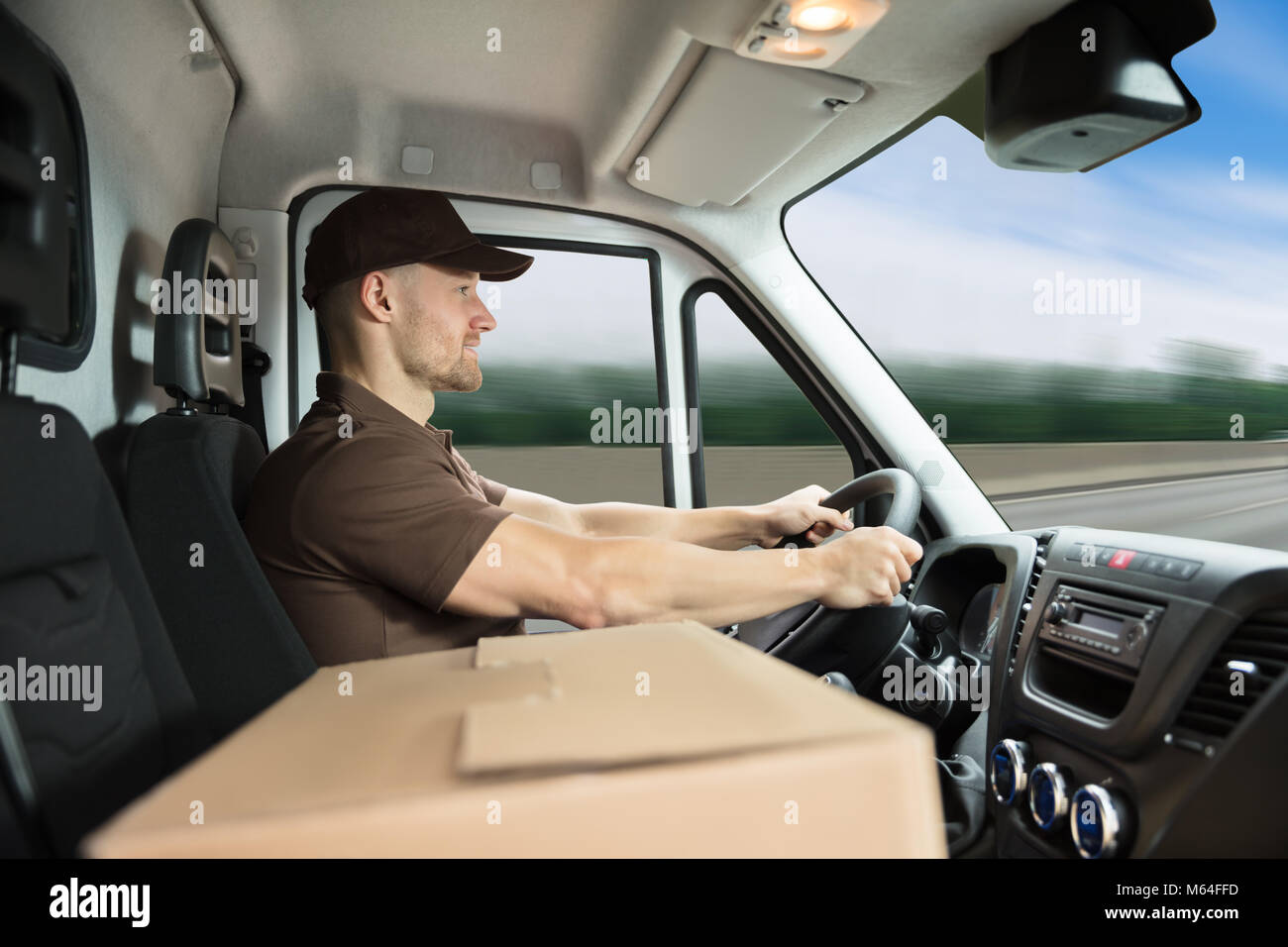 Portrait Of A Smiling Young Delivery Man Sitting Inside Van With Cardboard Box - Stock Image