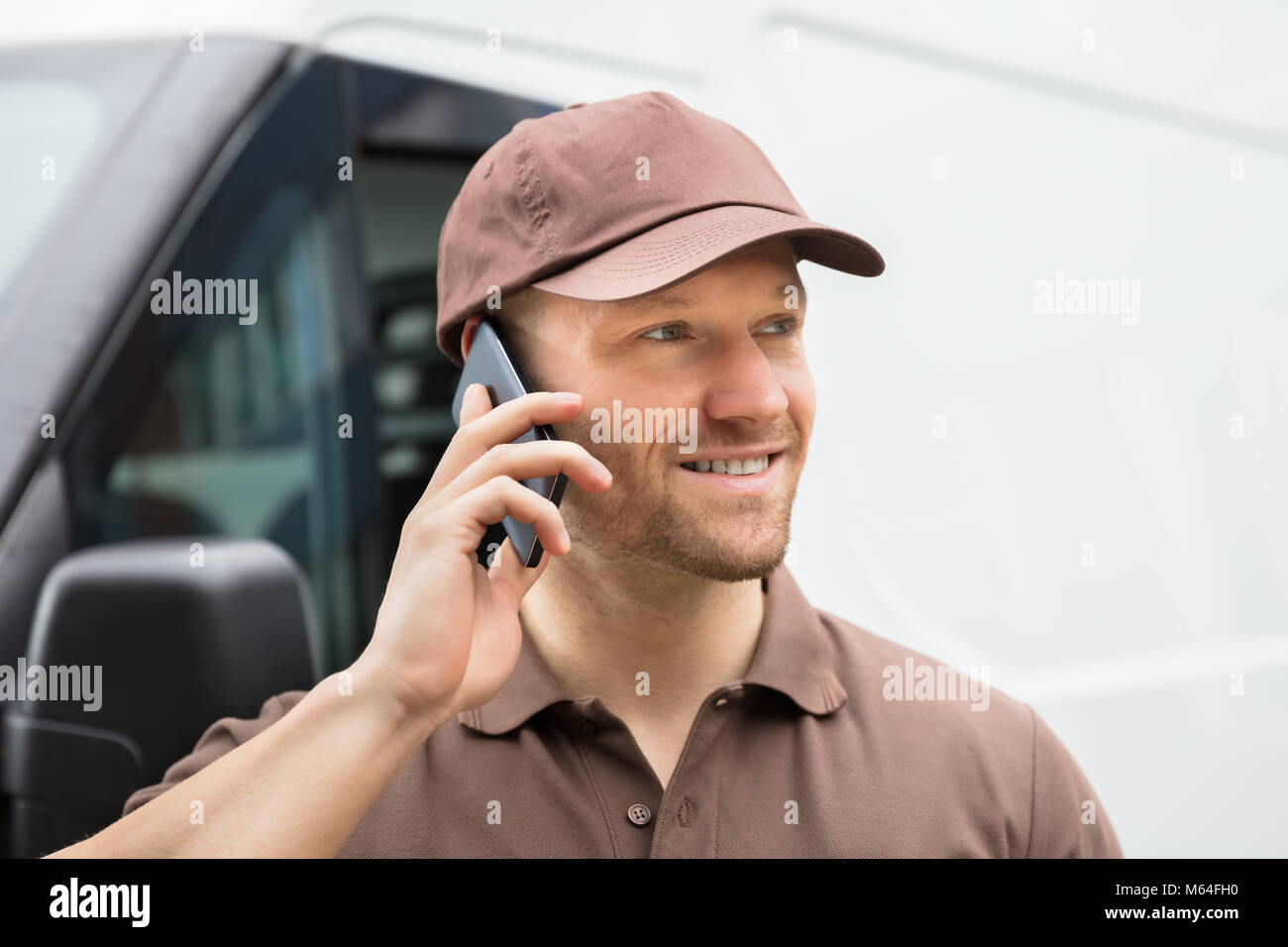 Close-up Of A Happy Young Delivery Man Talking On Mobile Phone - Stock Image