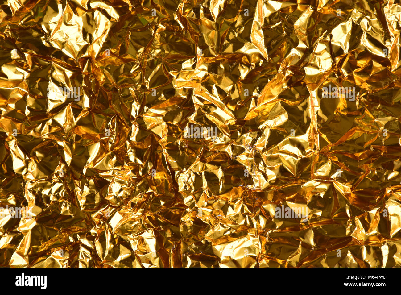 Screwed up  crumpled gold and silver foil - Stock Image