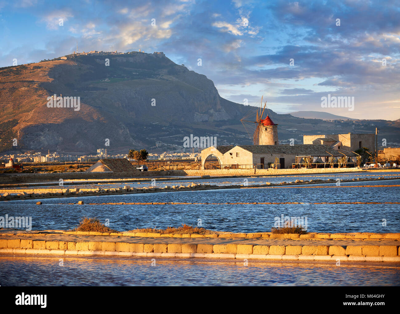Pictures & images of the salt pans of the Nubia Salt works Museum and Nubia wind mill with Erice on the hills - Stock Image