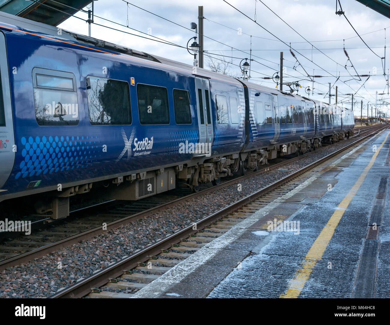 Close up of ScotRail local commuter train at Drem railway station in Winter with salt on station platform, East Stock Photo