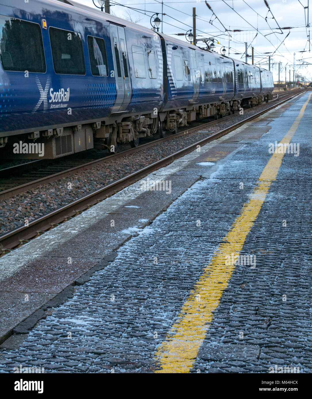 Close up of ScotRail local commuter train at Drem railway station in Winter with salt on station platform, East - Stock Image