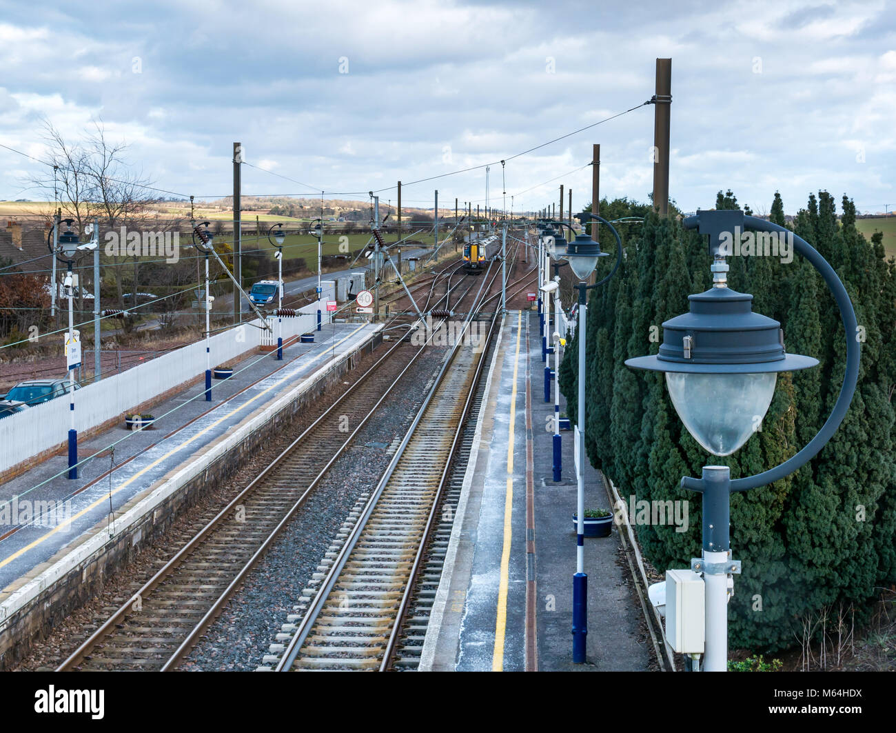 ScotRail local commuter train leaving Drem railway station, seen from above looking down on train tracks and overhead - Stock Image