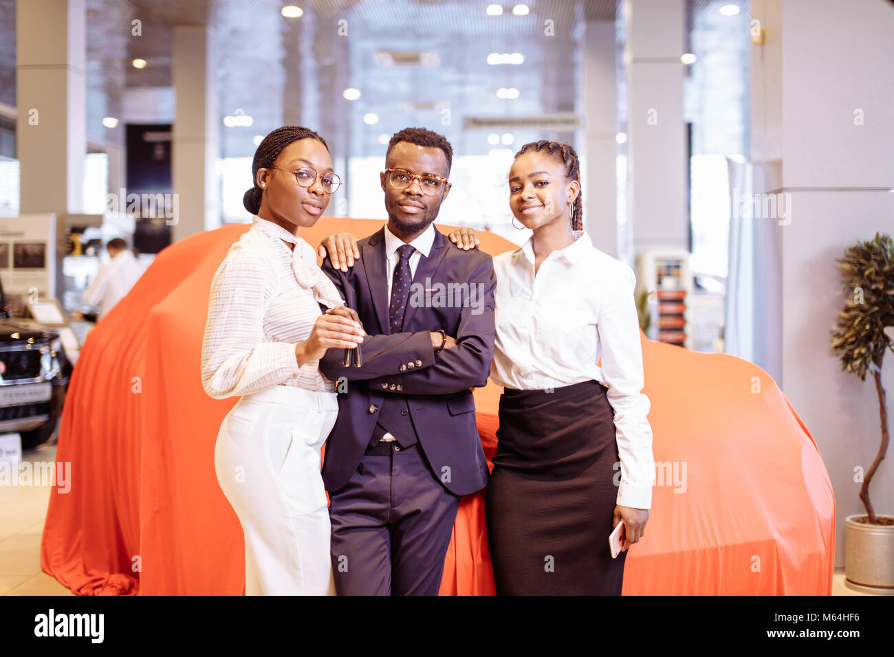 car salesman and two woman showing key of new car - Stock Image