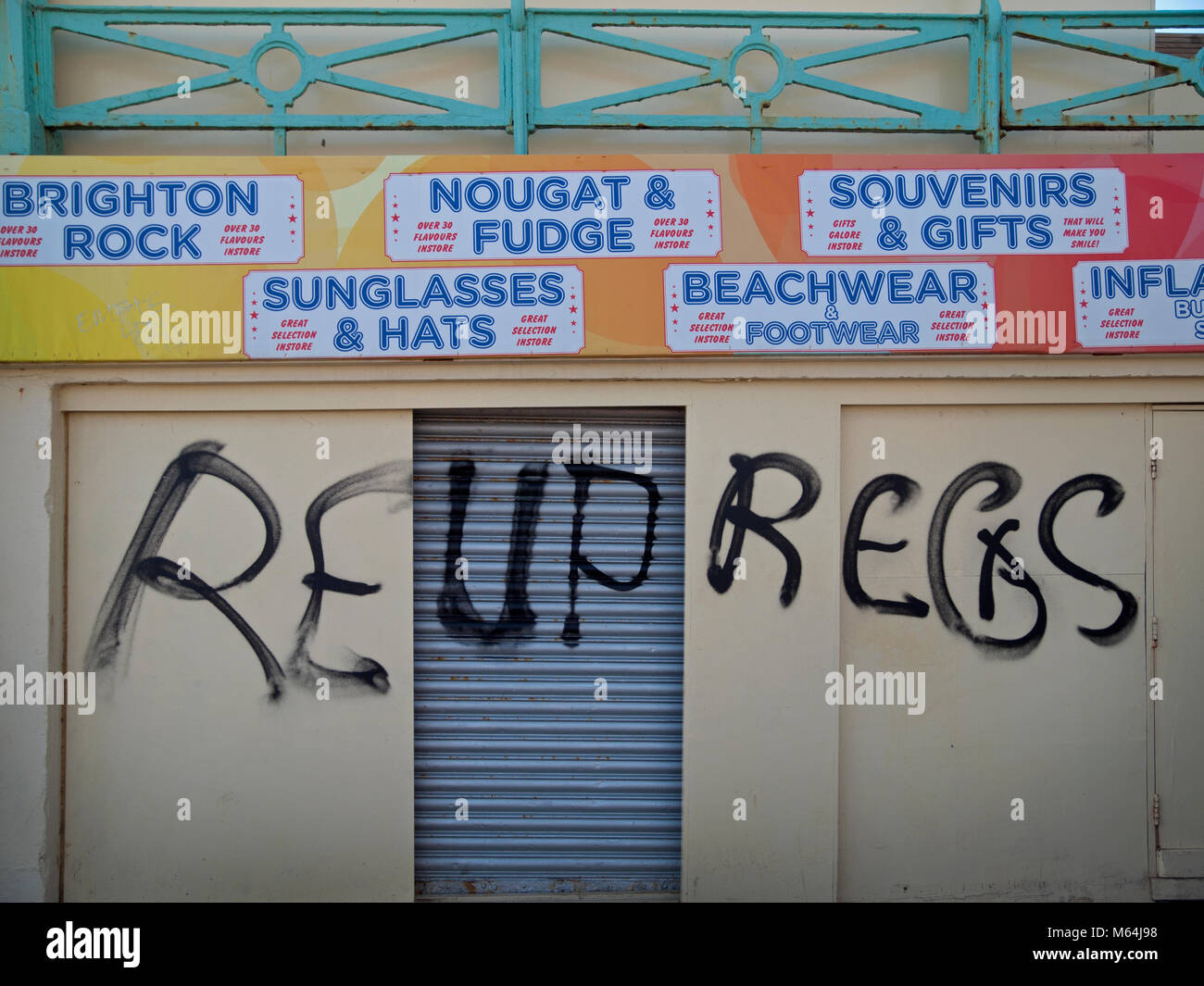 Obscure graffiti and signs for seaside essentials close to the beach in Brighton - Stock Image