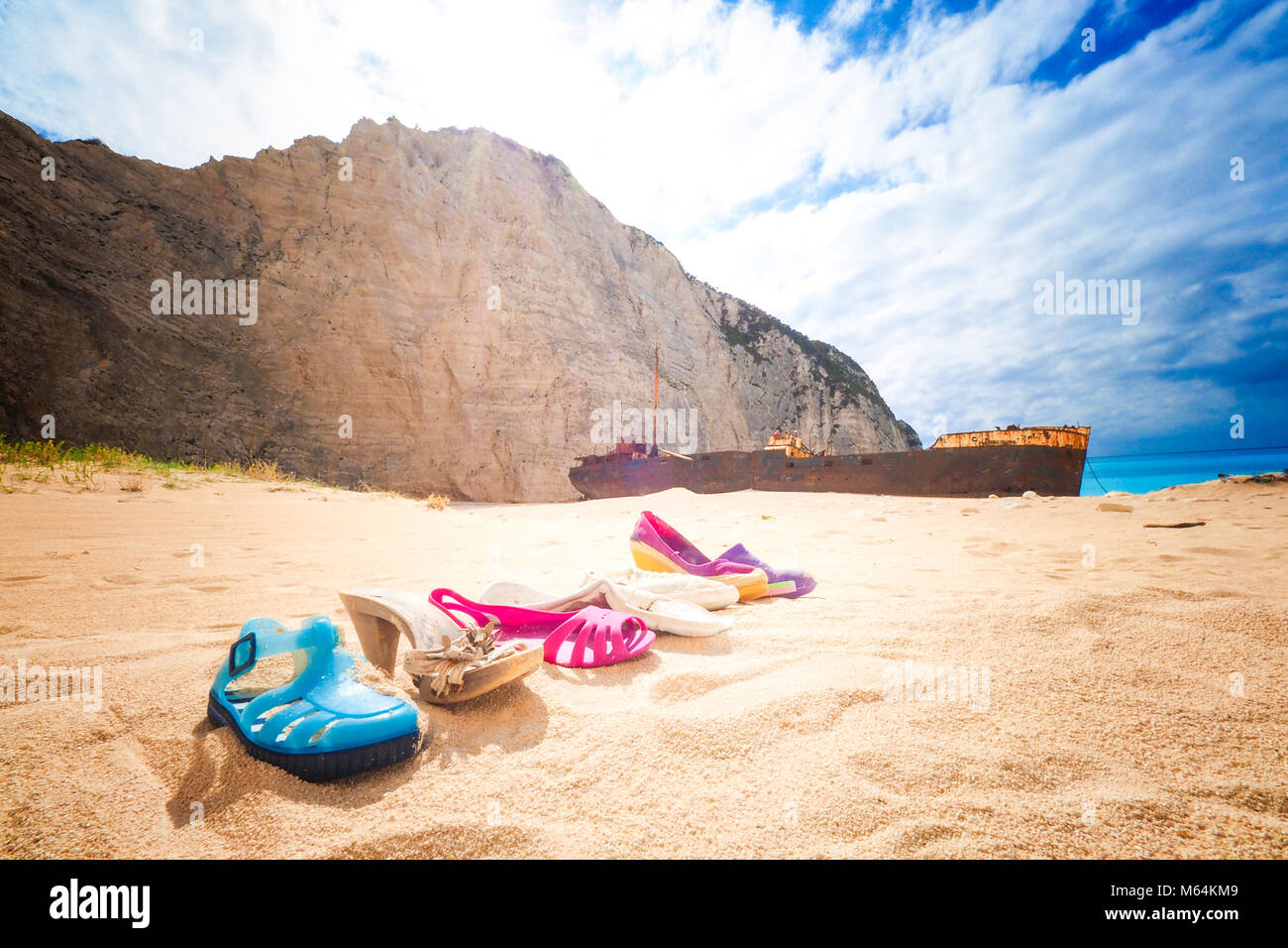 Trash left at Navagio beach, with Panagiotis shipwreck in back. Zakynthos, Greece. Artistic view. - Stock Image