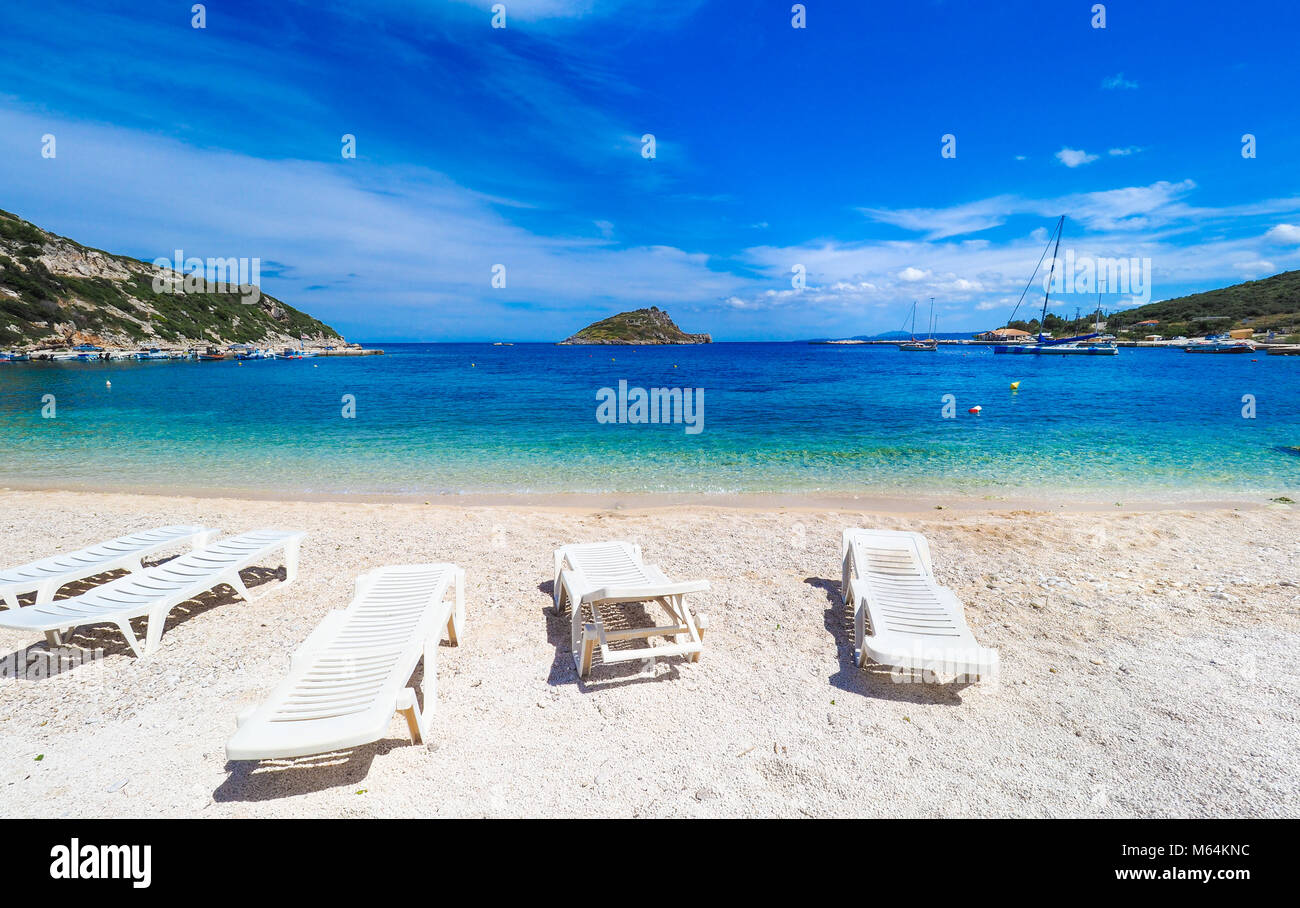 Sunny summer beach in Greece with sun beds and small boat - Stock Image