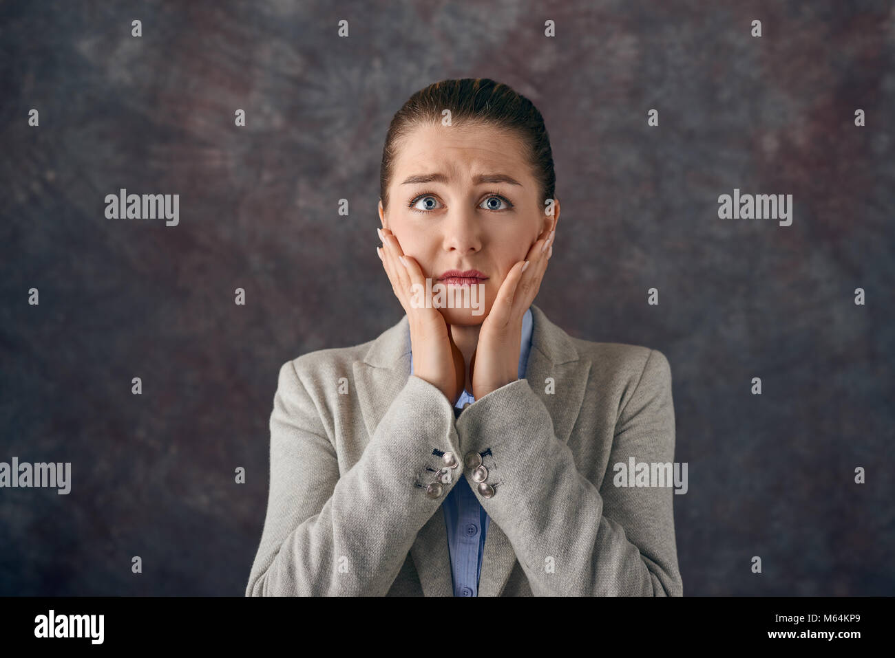 Dismayed upset young woman with her hands to her cheeks staring wide eyed at the camera with a tearful expression - Stock Image