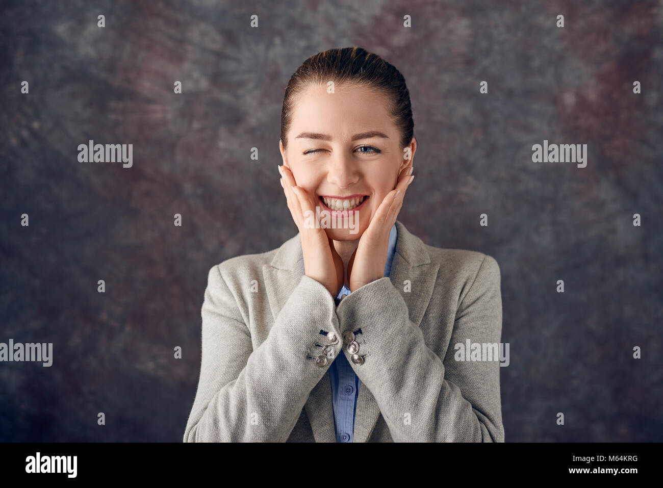 Cute attractive young woman winking as she grins happily at the camera while holding her hands to her cheeks over - Stock Image