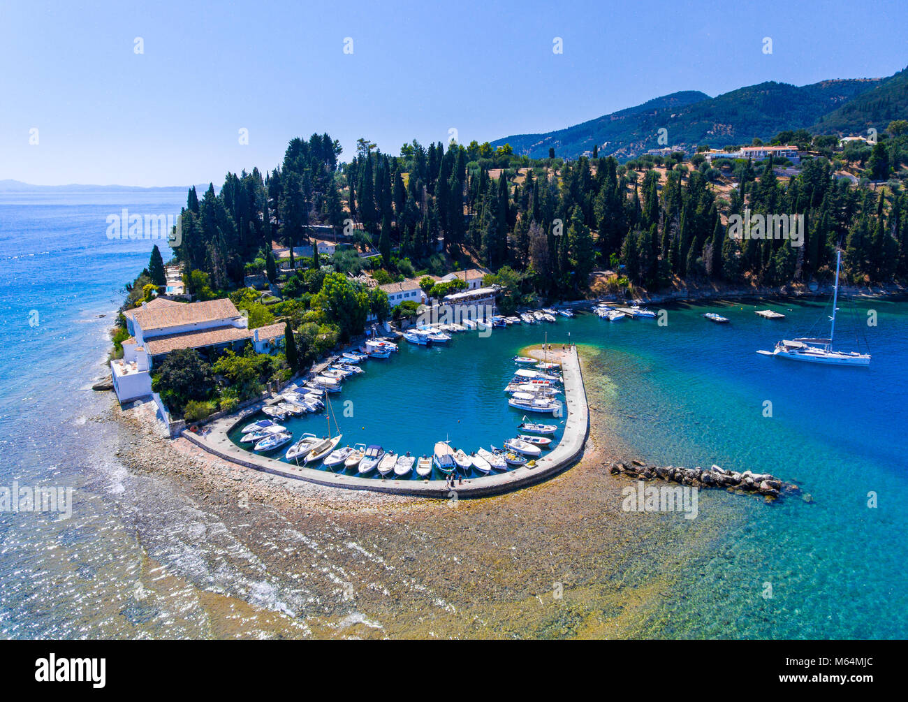 Kouloura old fishing village and beach. Corfu (Kerkyra) Island, Greece, Europe. Fishing boats and clear blue waters. Stock Photo