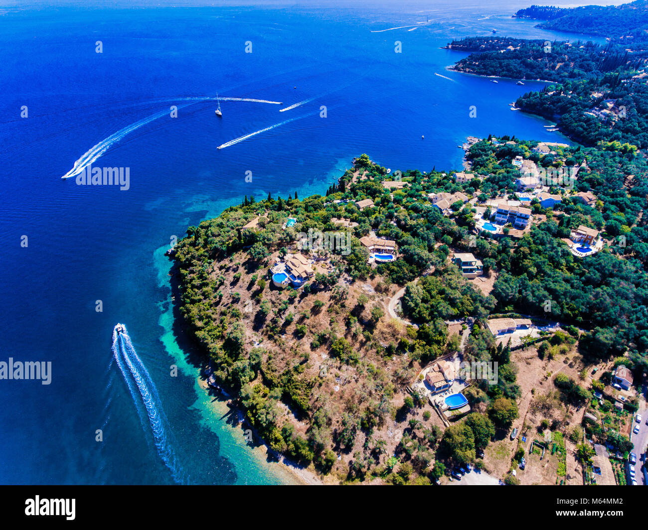 Corfu island clifs with traditional houses with swimming pool, yachts and clear blue waters. Kerkyra Island, Greece. Stock Photo