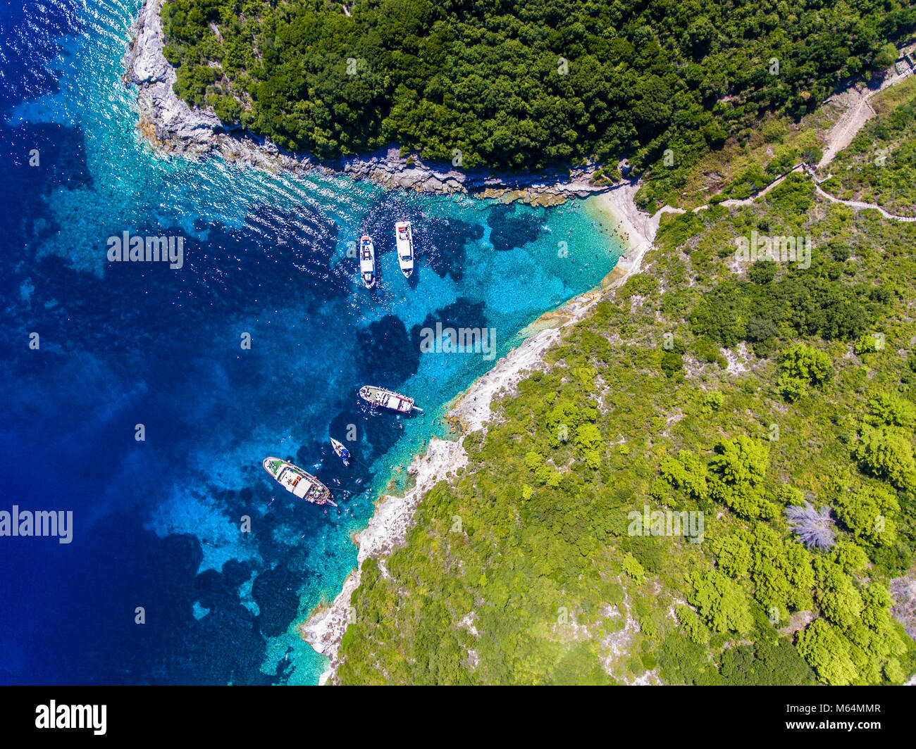 Antipaxos Island, Greece, with sandy beach, people swimming and yachts docked in the ethereal clear blue waters Stock Photo