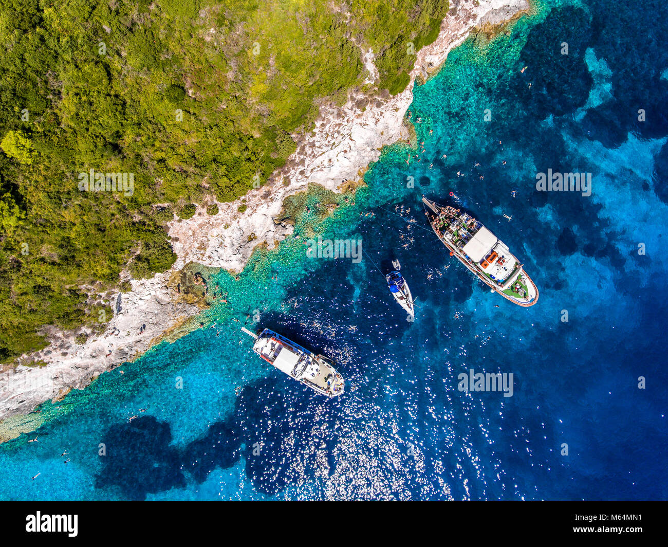 People swimming in the clear blue waters of Antipaxos Island, near Corfu - Kerkyra, Greece. Aerial view from a boat Stock Photo