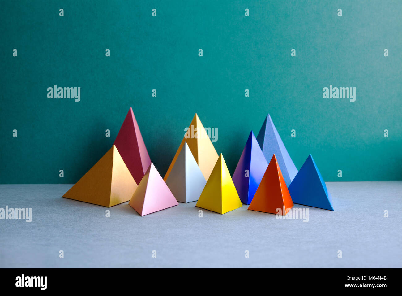 Colorful abstract geometric figures. Three-dimensional pyramid rectangular objects on green gray background. Yellow - Stock Image