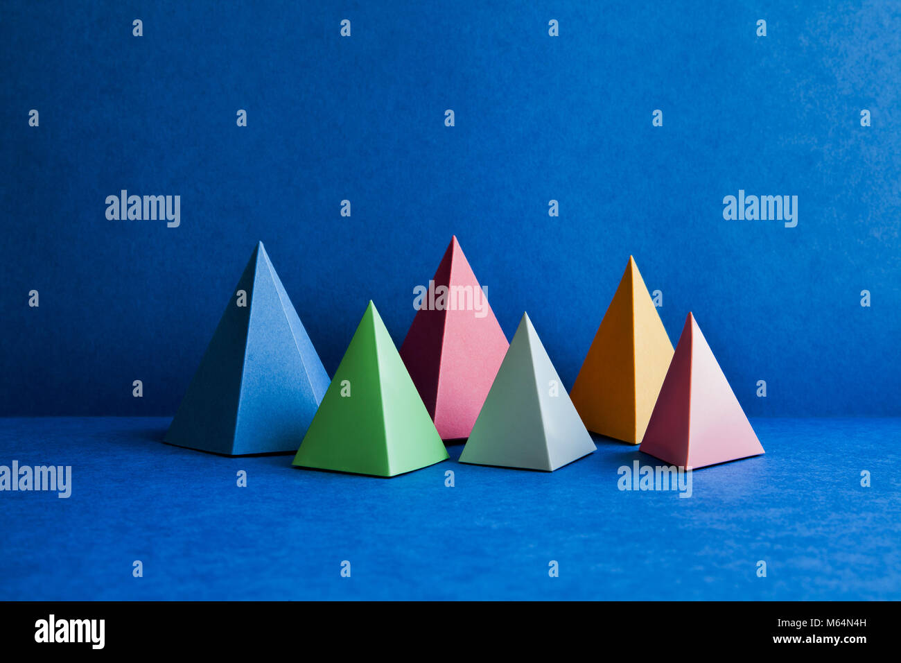 Platonic solid geometric figures. Three-dimensional pyramid rectangular objects on blue background. Yellow blue Stock Photo