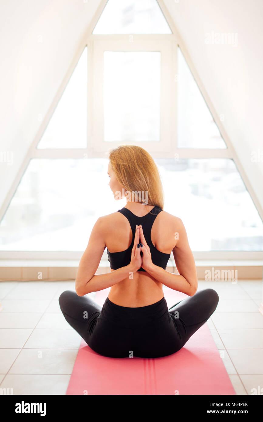 woman doing yoga in reverse prayer pose. Pashchima Namaskarasana - Stock Image