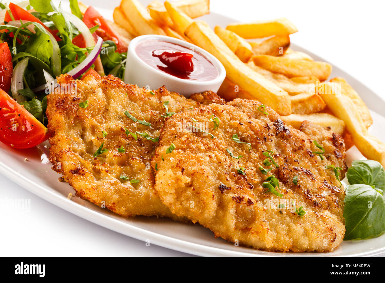 Fried pork chop, French fries and vegetables isolated on white background Stock Photo