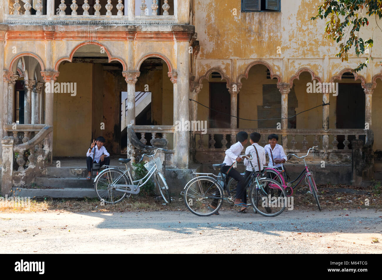 Children playing outside an old french colonial building, Angkor Borei, Kampot province Cambodia Asia - Stock Image