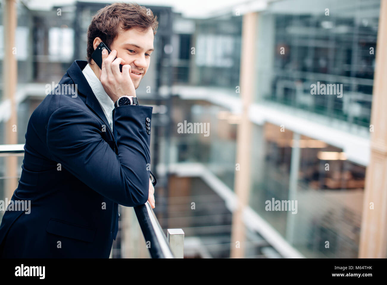 Business man walking while talking on mobile phone on his way to work - Stock Image