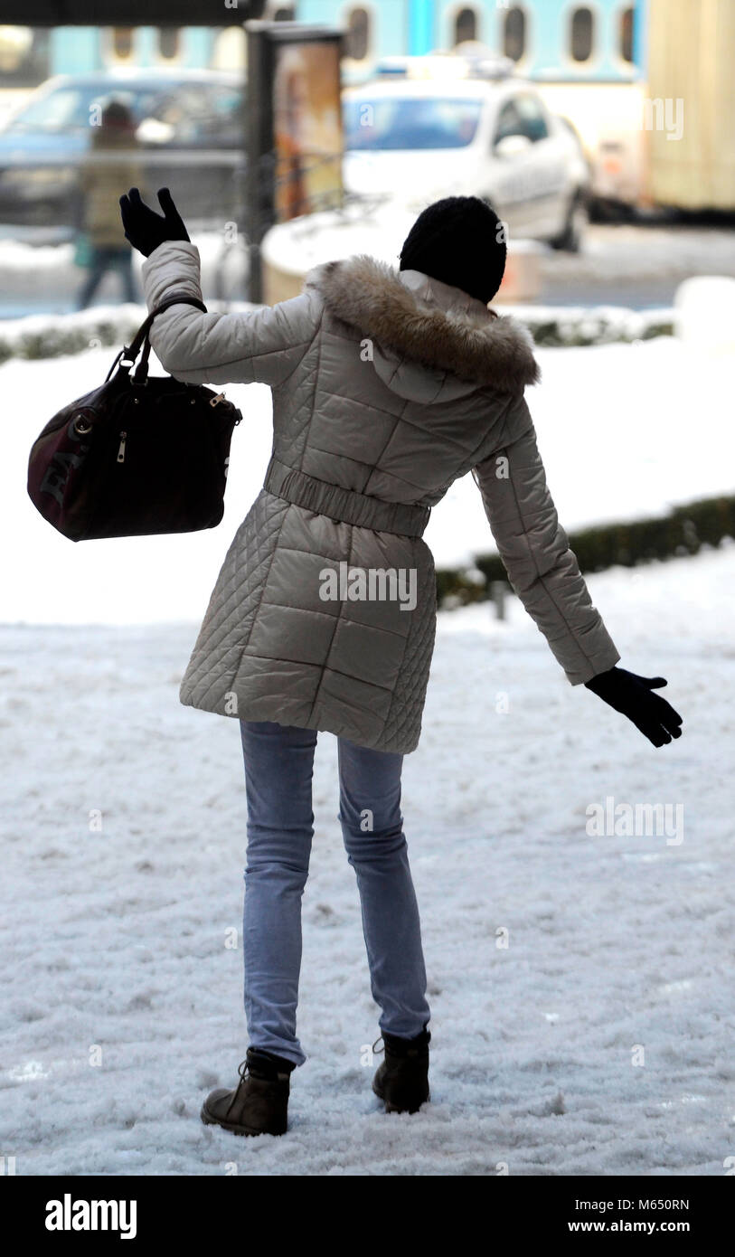 Young woman walking on slippery floor on snow - Stock Image