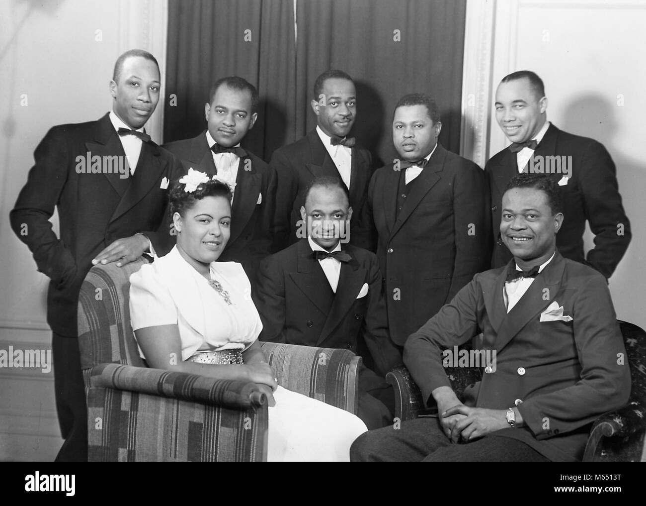 Black and white group portrait photograph of famous african american musicians including singer songwriter billie holiday wearing a pale dress and a