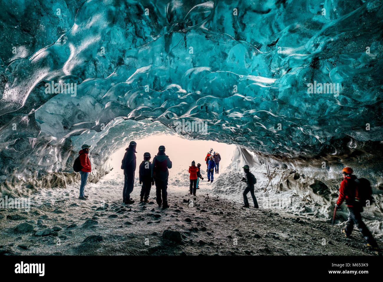 Tourists in The Crystal Cave, Breidamerkurjokull Glacier, Iceland. Emerald Blue Ice and Ash is part of Breidamerkurjokull. - Stock Image