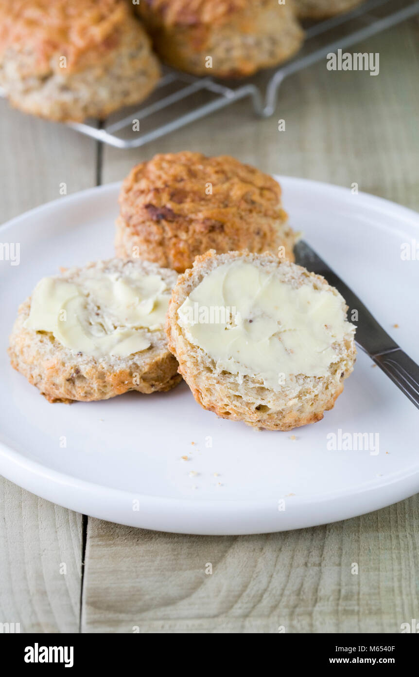 Freshly baked cheese scones spread with butter. - Stock Image