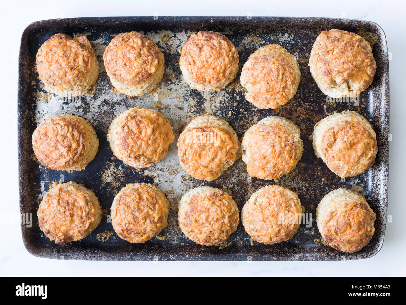 Freshly baked cheese scones on a baking tray. - Stock Image