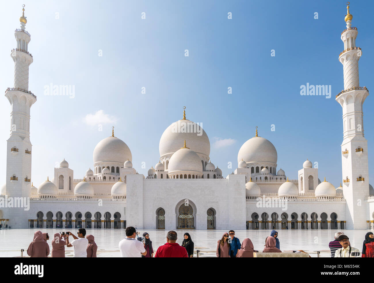 28th December 2017 - Abu Dhabi, UAE. Tourists take photographs and selfies in front of a gorgeous Sheikh Zayed mosque. - Stock Image