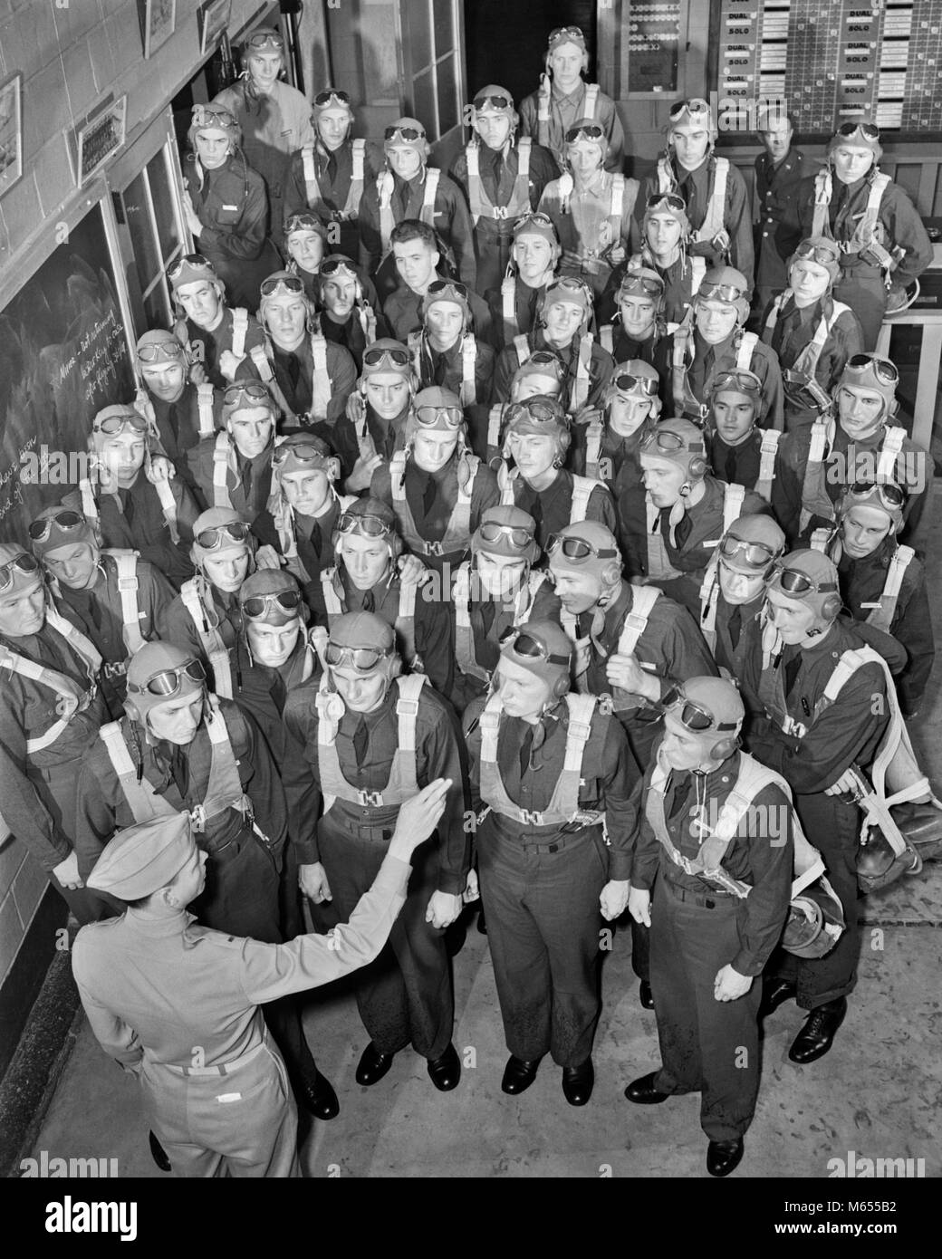 1940s NEW AVIATION OFFICERS GET LAST MINUTE PARACHUTE INSTRUCTION BEFORE TRAINING FLIGHT - a1603 HAR001 HARS STRENGTH - Stock Image
