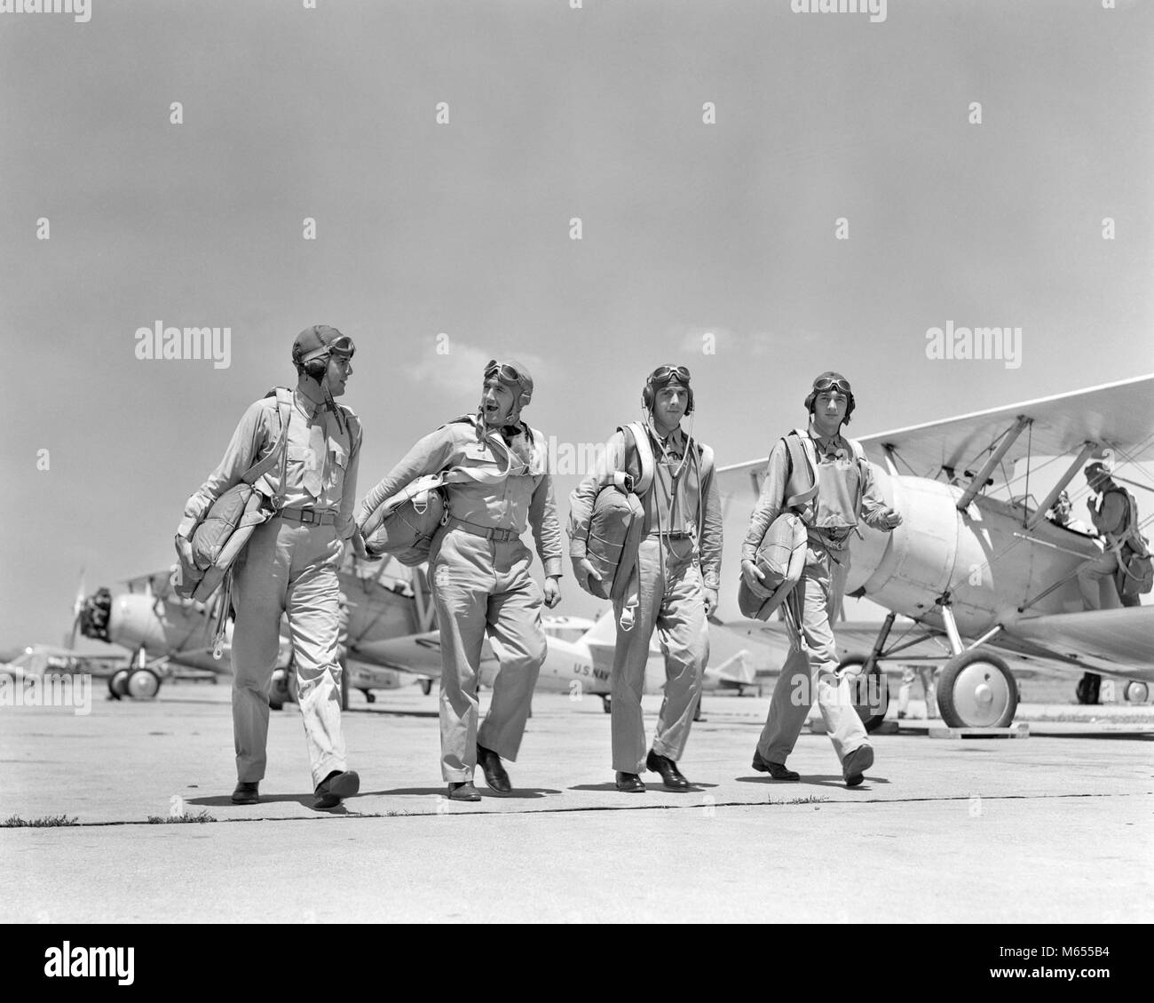 1940S FOUR U.S. NAVY PILOTS WALKING TOGETHER ON TARMAC RETURNING FROM AIR MANEUVERS AT THE PHILADELPHIA NAVY YARD - Stock Image