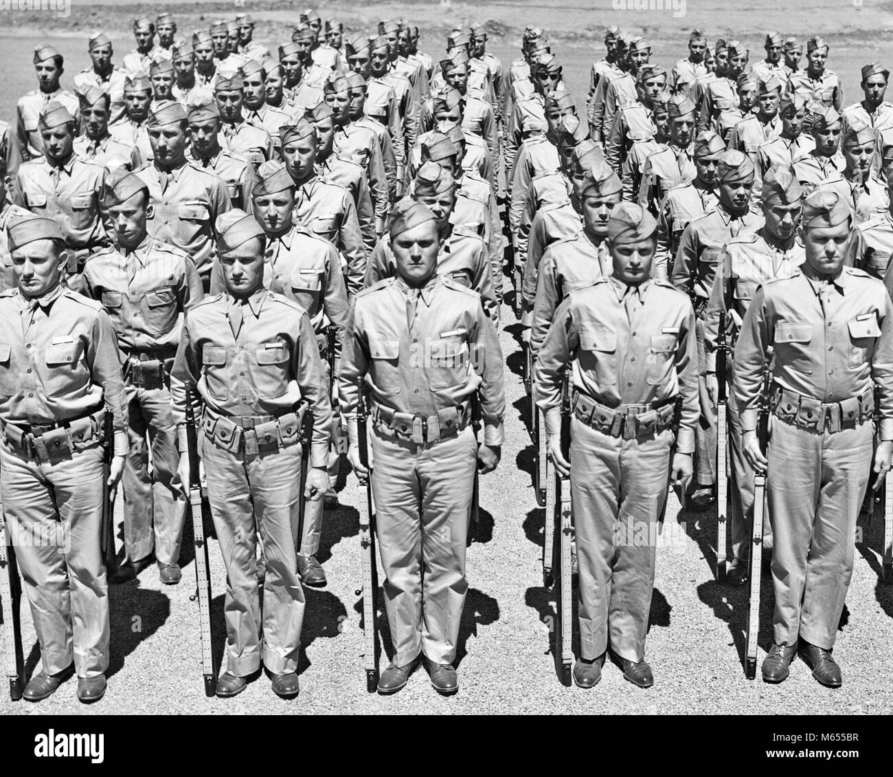 1940s ROWS OF AMERICAN WORLD WAR II SOLDIERS STANDING AT ATTENTION WITH RIFLES LOOKING AT CAMERA - a2433 HAR001 - Stock Image