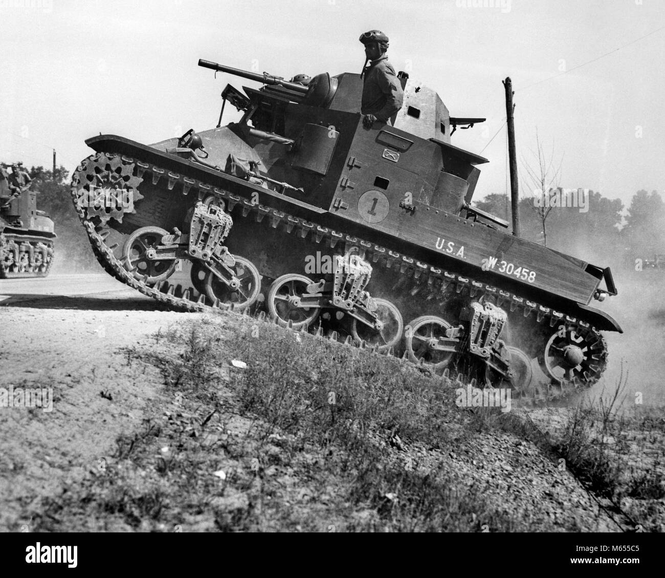 1930s 1940s SMALL AMERICAN ARMY M2 LIGHT TANK ON AN INCLINE BY SIDE OF ROAD - a2434 HAR001 HARS EXCITEMENT WORLD - Stock Image