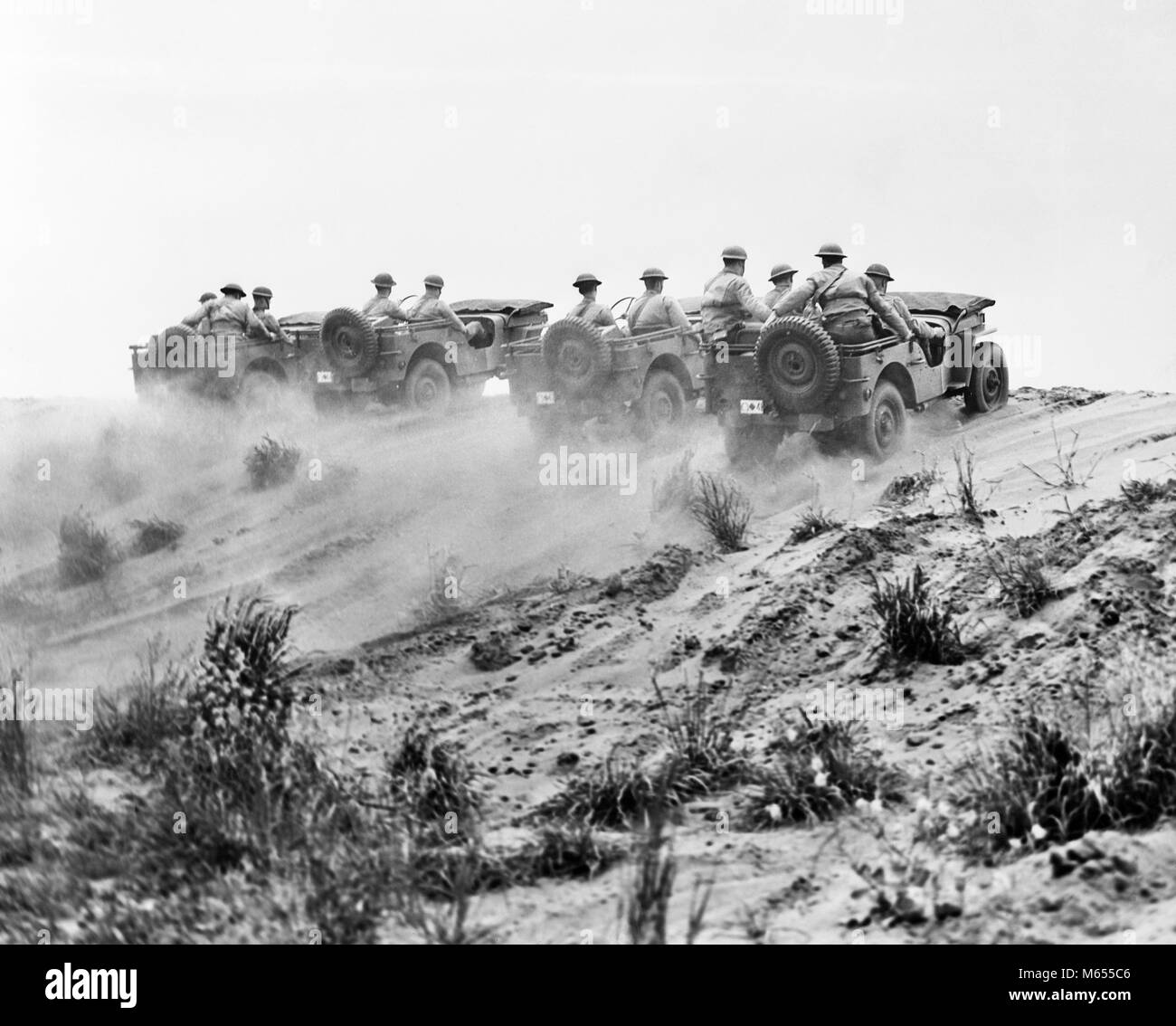 1940s ARMY SOLDIERS RIDING JEEPS IN FORMATION GOING UP A DUSTY HILL - a2739 HAR001 HARS EXCITEMENT LOW ANGLE WORLD - Stock Image