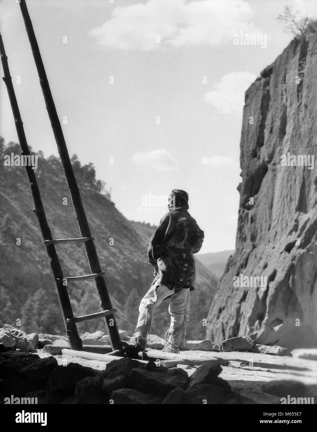 1930s NATIVE AMERICAN INDIAN MAN BY KIVA LADDER FRIJOLES CANYON CEREMONIAL KIVA BANDELIER NATIONAL MONUMENT NEW - Stock Image